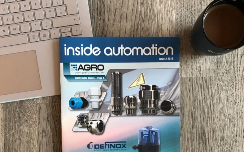 Ttable with OEM Automatic's customer magazine inside automation front cover in the centre, laptop keyboard top left, black mug top right
