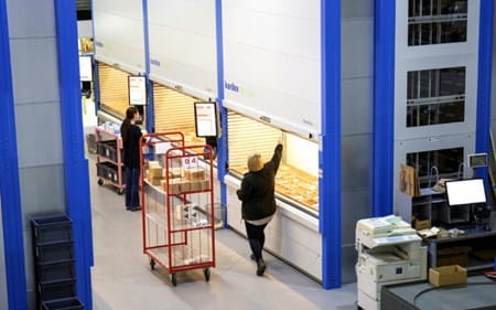 Warehouse with Kardex machines, two warehouse operatives picking stock